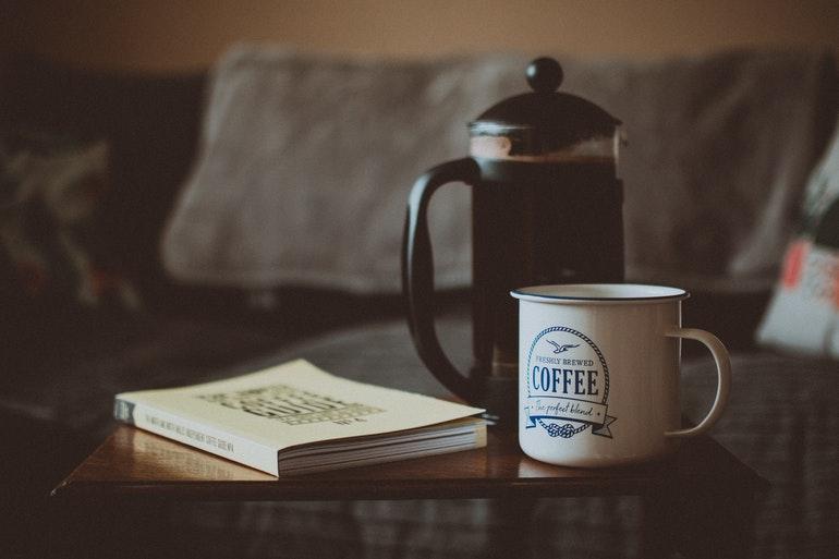 french press alongside coffee mug and good book